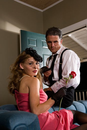 Stock Photo: 1574R-28633 Portrait of a mid adult man holding hand of a young prostitute on sofa