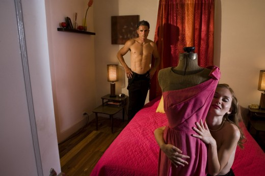 Topless young prostitute holding a mannequin in the bedroom while a mid adult man standing by bed : Stock Photo