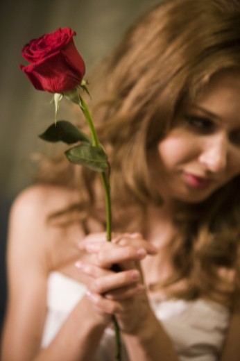 Contemplative young prostitute holding a rose : Stock Photo