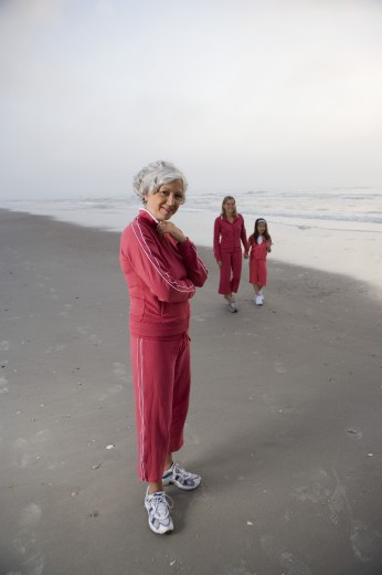 Portrait of a mature woman standing while other walking at the beach : Stock Photo