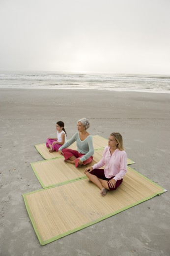 Grandmother exercising with daughter and granddaughter on a mat at the beach : Stock Photo