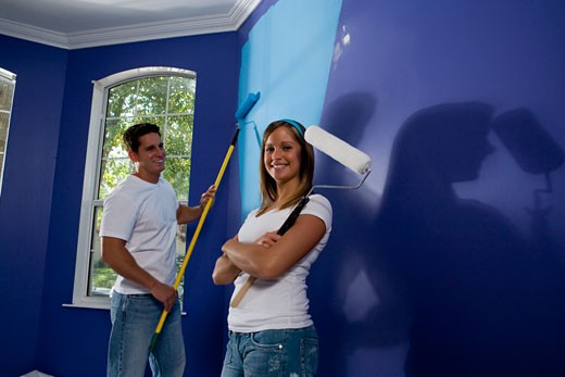 Portrait of a cheerful young woman holding paint roller with arms crossed while young man painting wall : Stock Photo