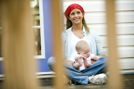 Stock Photo: 1574R-28909 Young woman holding her baby on lap
