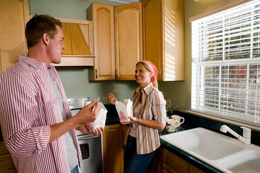 Stock Photo: 1574R-28963 Cheerful mid adult couple eating fast food in the kitchen