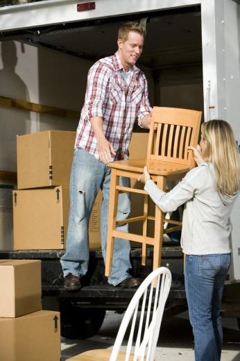 Stock Photo: 1574R-29014 Mid adult couple unloading chairs and cardboard boxes from a moving van