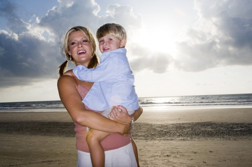 Cheerful young woman holding her son at the beach : Stock Photo