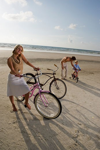 Parents with son riding cycle at the beach : Stock Photo