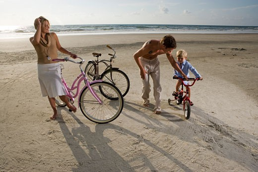 Stock Photo: 1574R-29105 Parents with son riding cycle at the beach