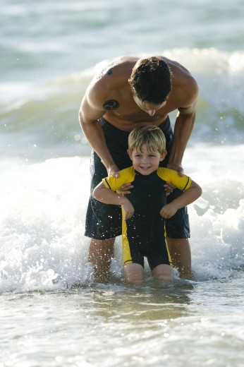 Father holding his son in water at the beach : Stock Photo