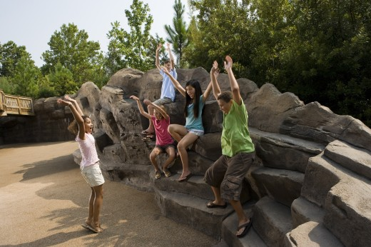 Stock Photo: 1574R-29211 Teenagers with their arms raised sitting on rocks and playing