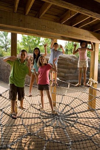 Portrait of teenagers standing on a net tied to the wooden columns and waving hands : Stock Photo