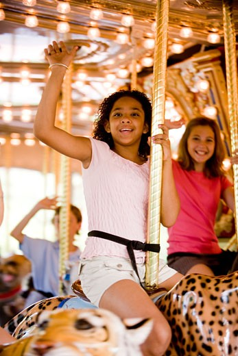 Portrait of cheerful teenage girls sitting on a carousel and waving hands : Stock Photo