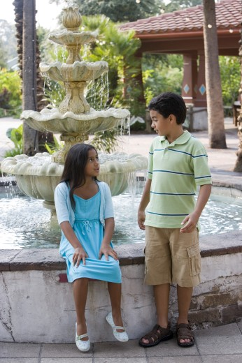 Girl sitting by water fountain while boy standing  : Stock Photo