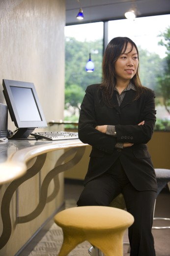 Businesswoman standing in an office by computer : Stock Photo