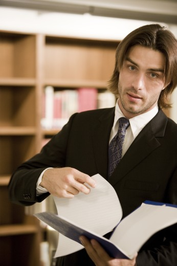Stock Photo: 1574R-30632 Portrait of a businessman holding a file in an office
