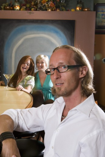 Stock Photo: 1574R-30670 Portrait of mature man sitting by bar counter while wife and daughter behind