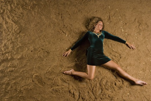 Overhead view of a young woman lying on sand : Stock Photo