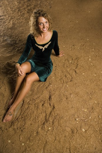 Portrait of a young woman sitting on sand : Stock Photo