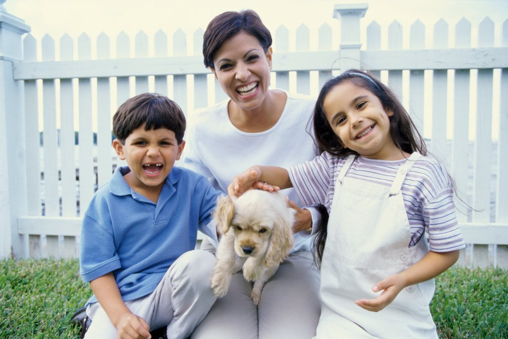 Portrait of a mother holding a puppy smiling with her two children : Stock Photo