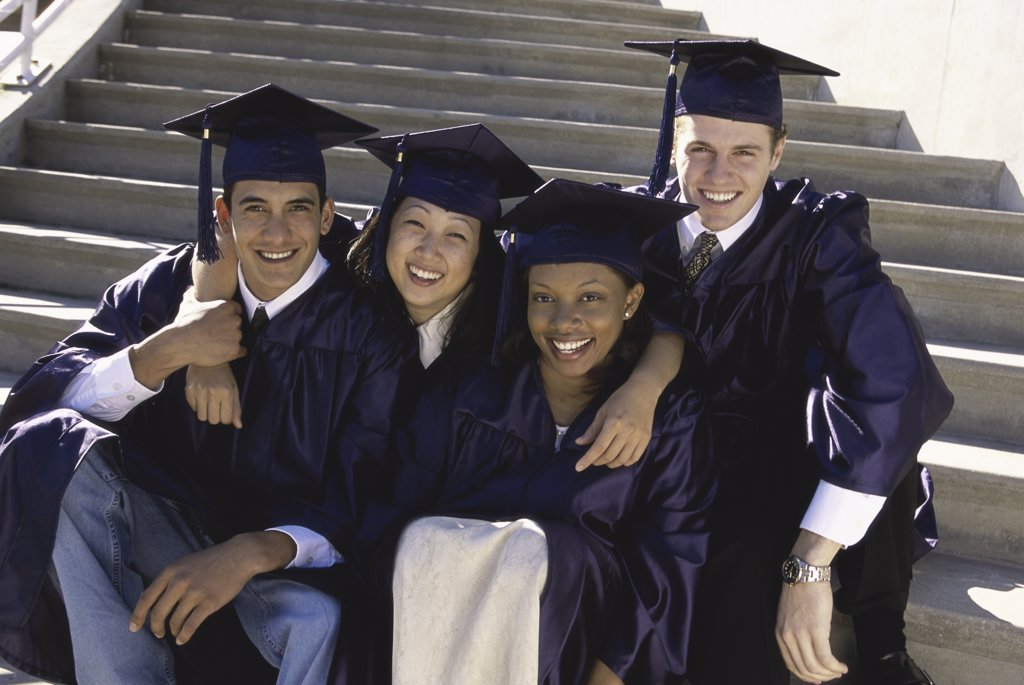 Portrait of a group of four young graduates sitting on stairs : Stock Photo