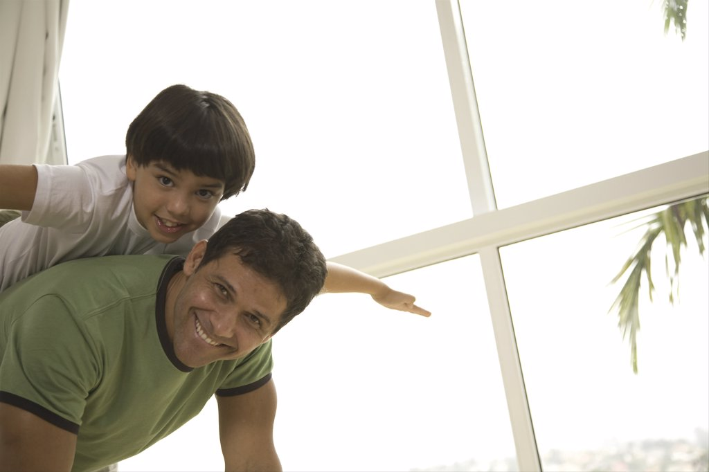 Boy riding piggyback on his father : Stock Photo