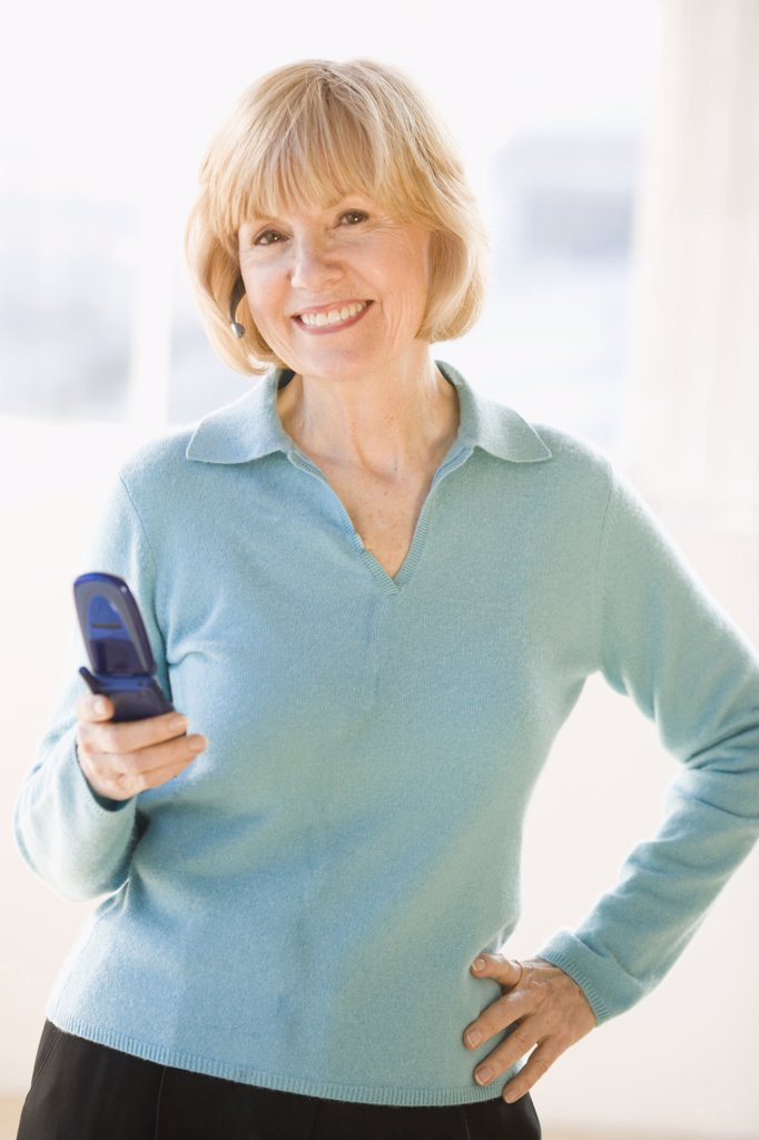 Businesswoman operating a mobile phone and smiling : Stock Photo