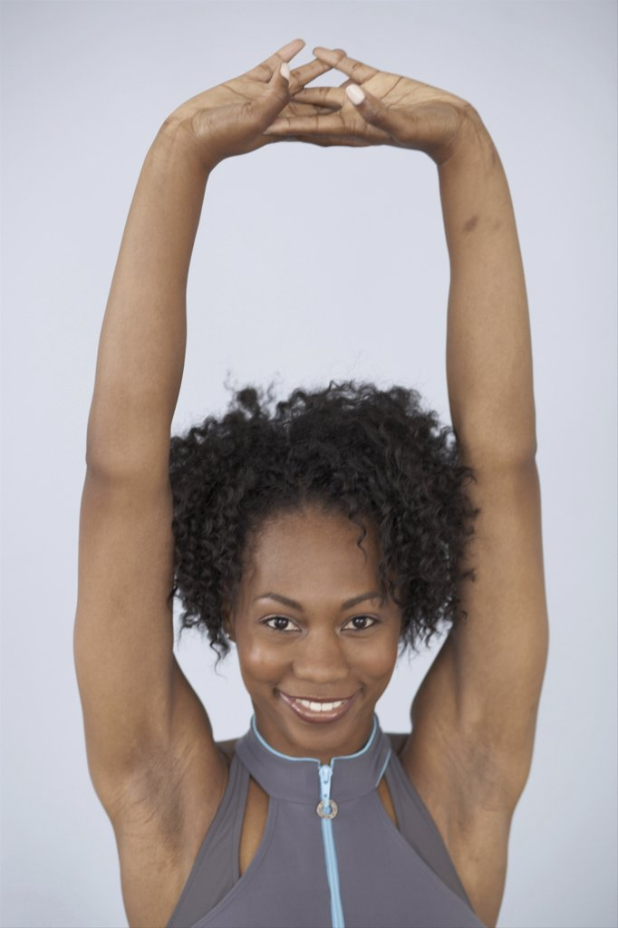 Portrait of a young woman smiling with her arms raised : Stock Photo