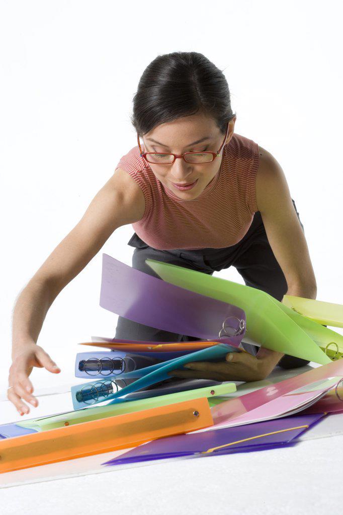 Businesswoman picking up ring binders : Stock Photo