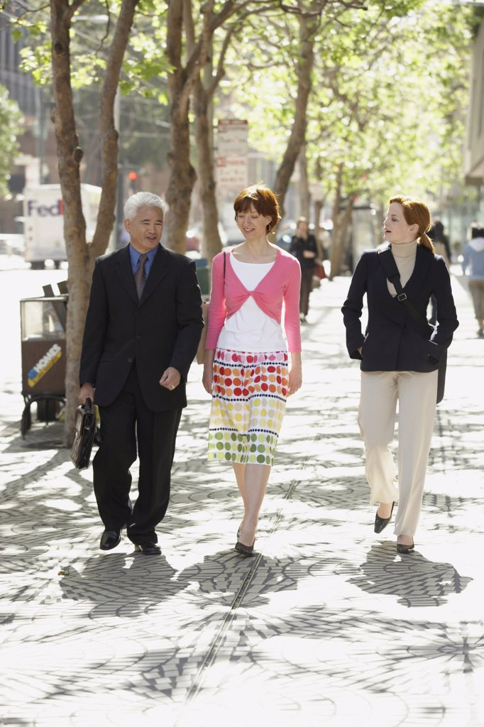 Stock Photo: 1574R-33401 Businessman with two businesswomen walking on a sidewalk