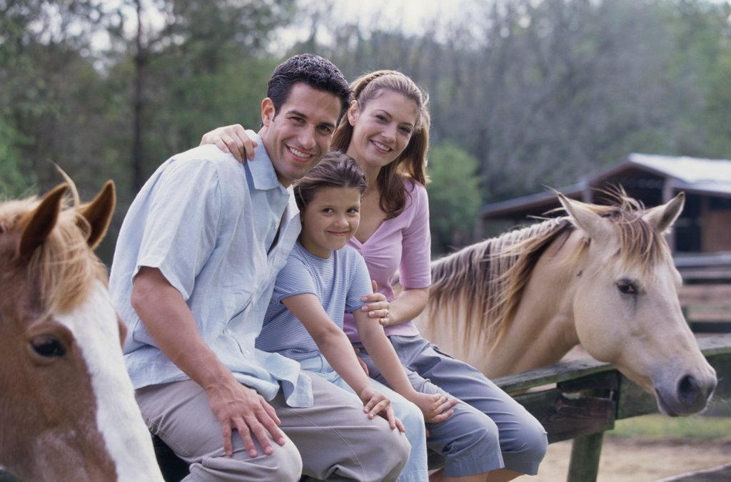 Portrait of parents with their daughter sitting on the fence of a stable : Stock Photo