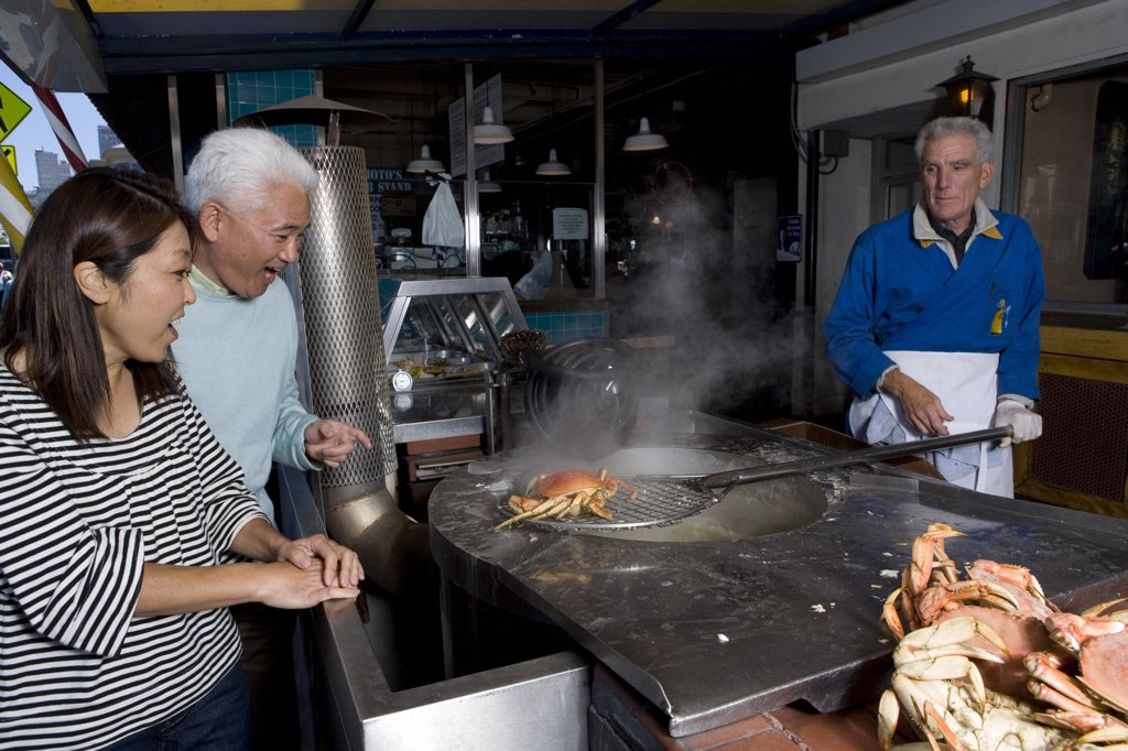 Mature couple standing and looking at crabs being cooked by a mature man in a restaurant, Fisherman's Wharf, San Francisco, California, USA : Stock Photo