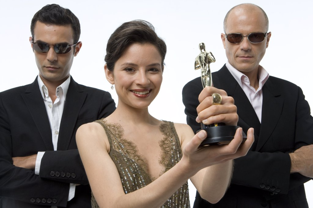 Portrait of a young woman holding a trophy with a young man and a mature man standing behind her : Stock Photo