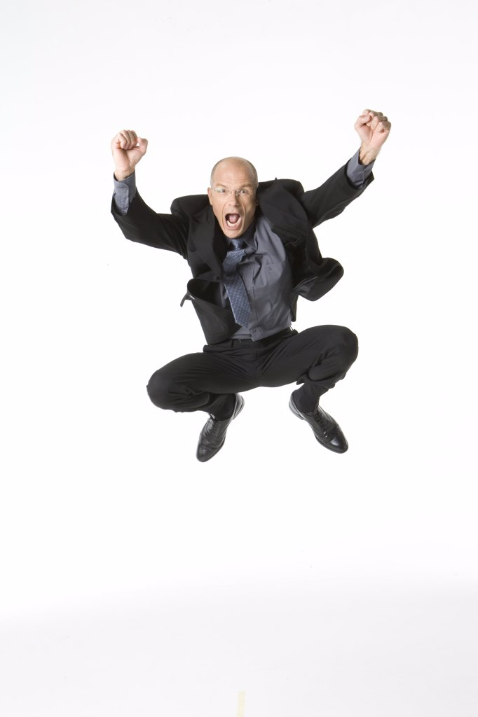 Businessman jumping into the air and looking excited : Stock Photo