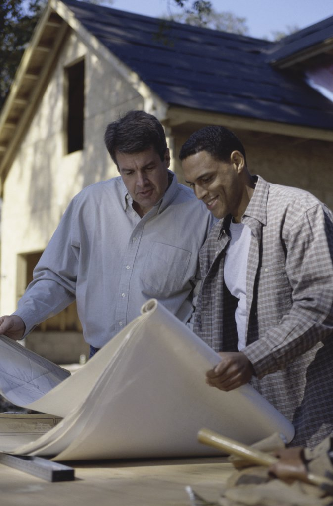 Two architects discussing blueprints at a construction site : Stock Photo