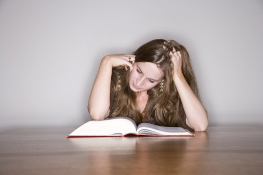 Young woman studies in the library : Stock Photo