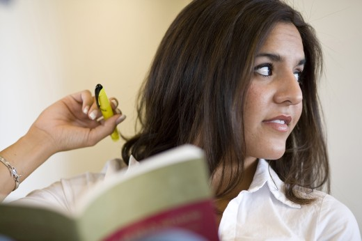 Young woman reading or studying in library : Stock Photo