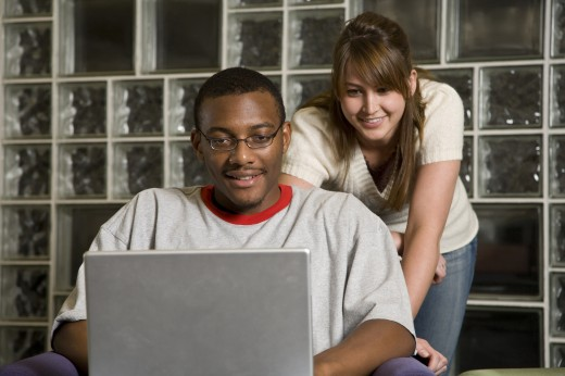 Stock Photo: 1574R-35447 Young man and woman using a laptop in a library