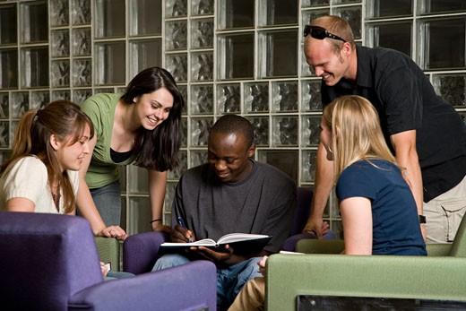 Group of young adults study together in a library : Stock Photo