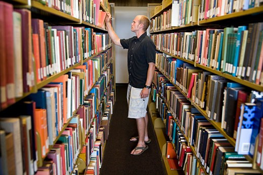 Stock Photo: 1574R-35473 Young man looks for a book in the library shelves