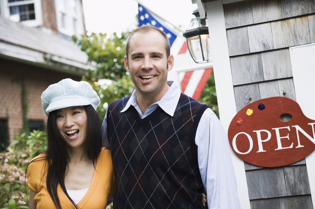 Couple standing beside an Open sign : Stock Photo