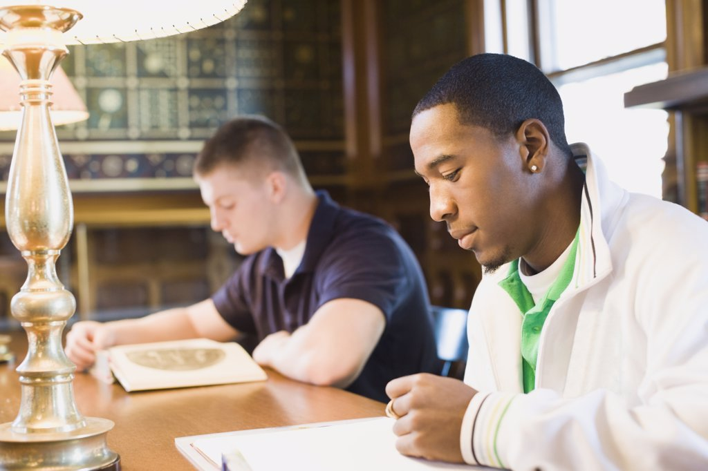 Students reading in a library : Stock Photo