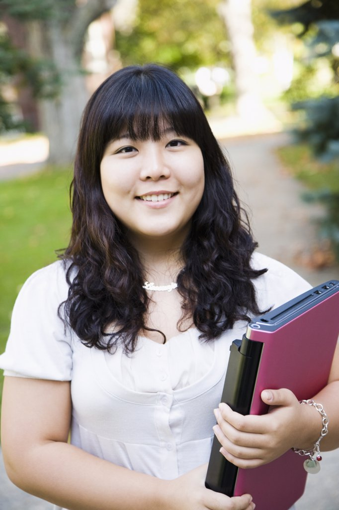 Student holding a file and smiling : Stock Photo