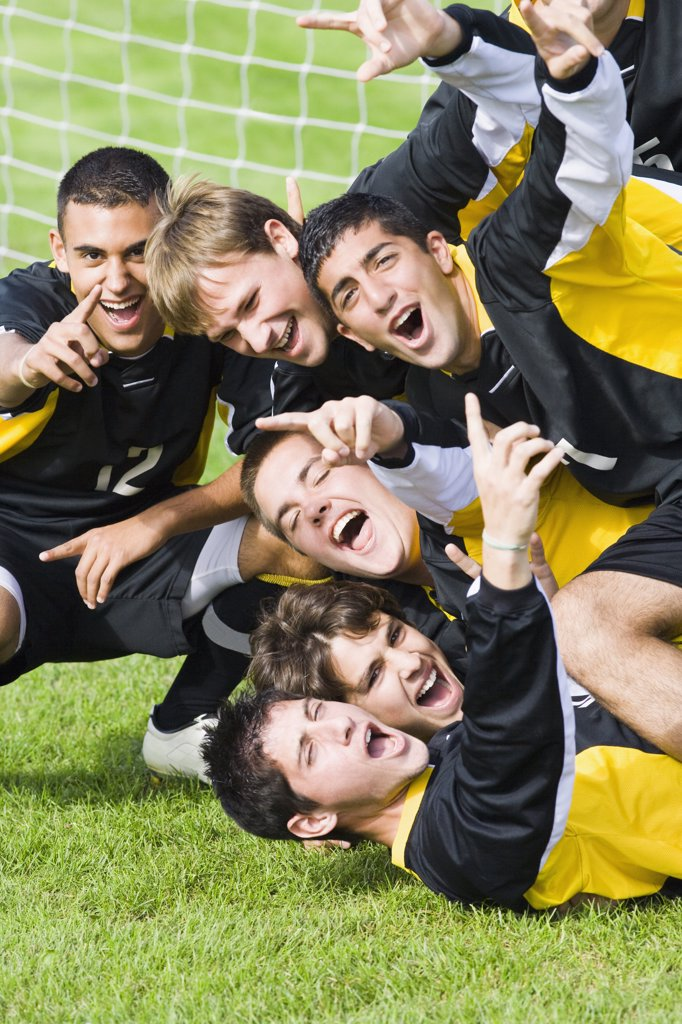 Soccer players cheering in front of a goal post in a soccer field : Stock Photo