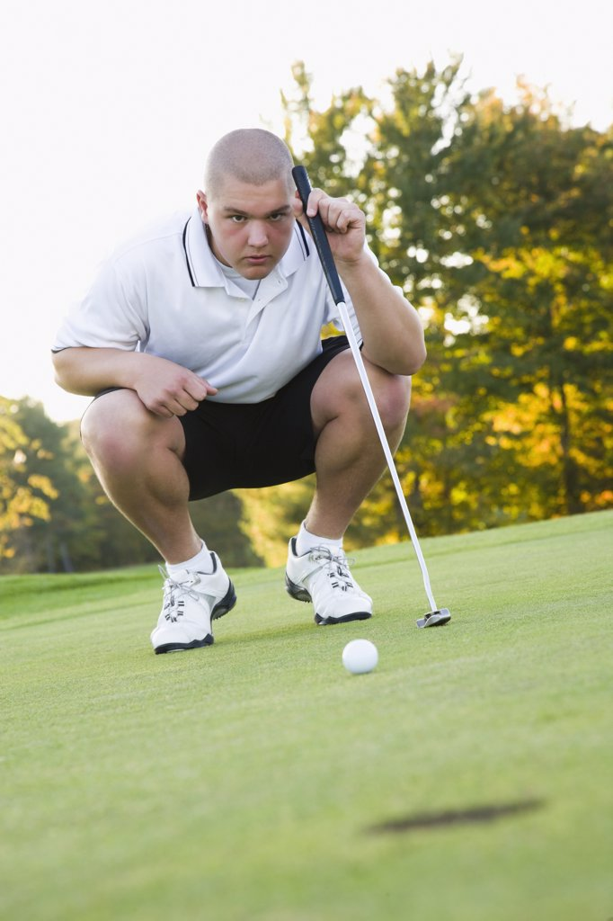 Stock Photo: 1574R-36324 Man looking at hole in a golf course