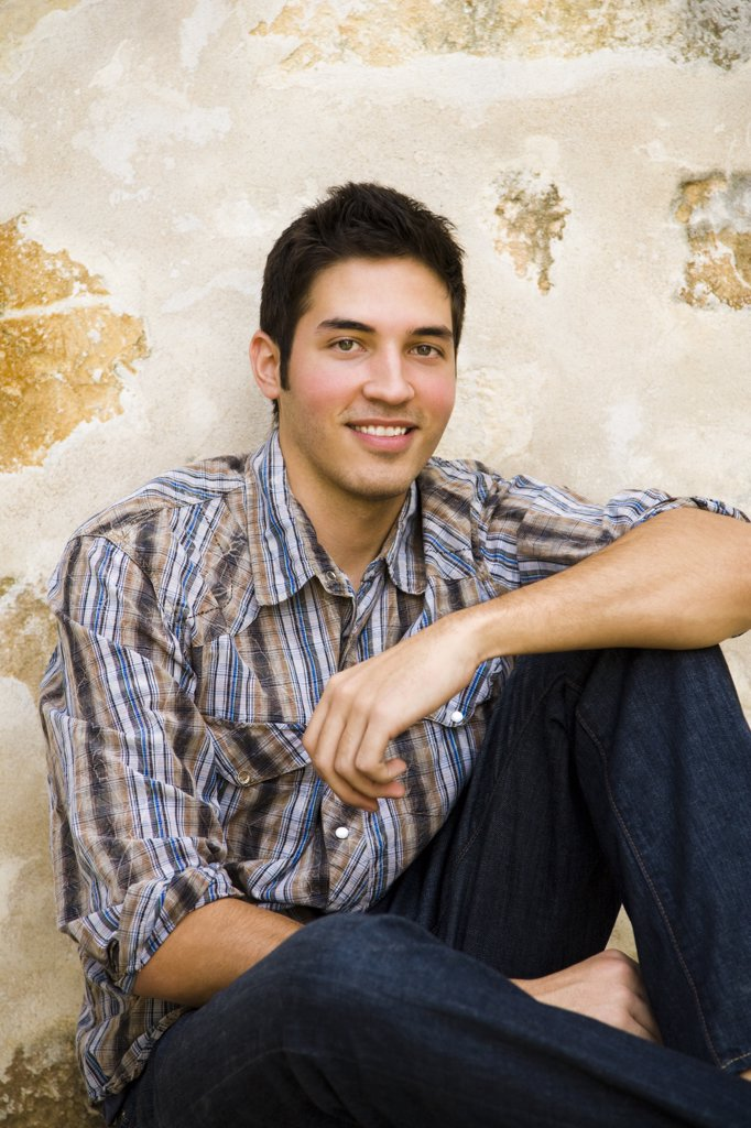 Portrait of a man sitting against a wall and smiling : Stock Photo