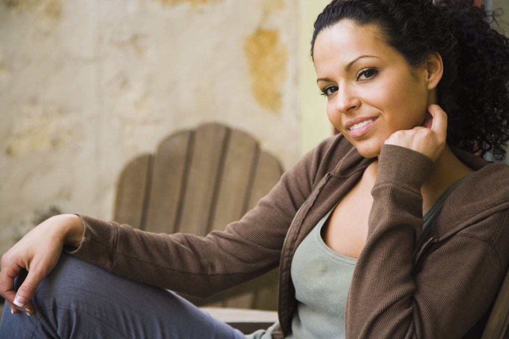Stock Photo: 1574R-36922 Portrait of a woman sitting on a chair and smiling
