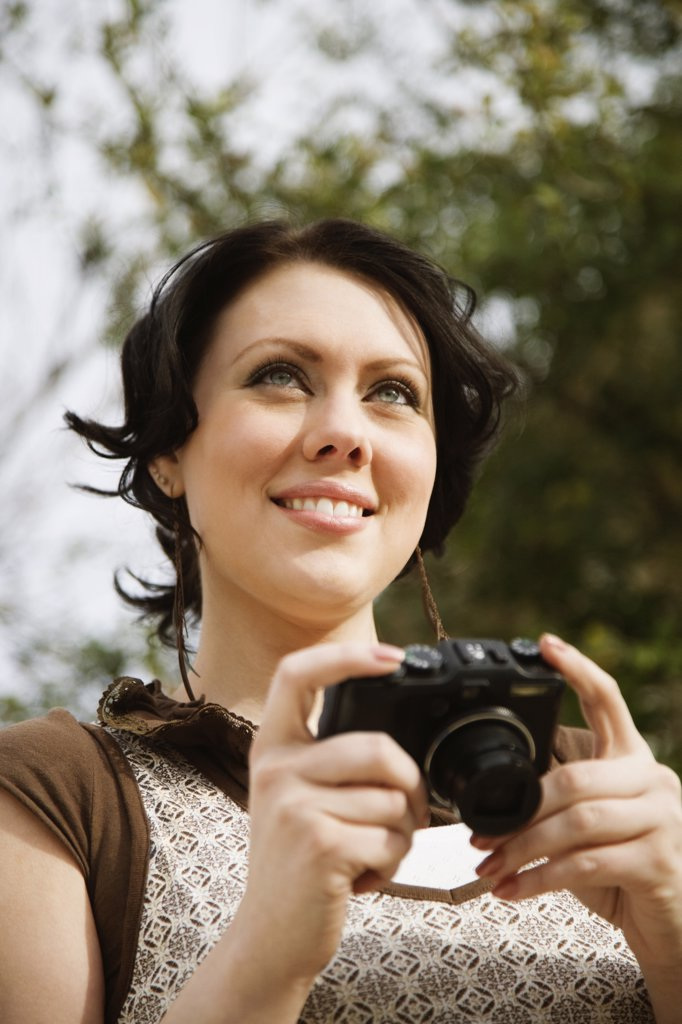 Woman holding a digital camera : Stock Photo