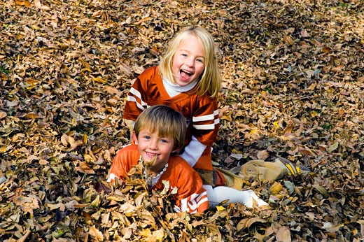 Boy and girl playing in fallen leaves : Stock Photo
