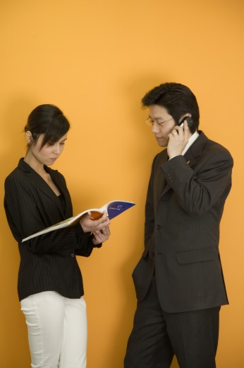 Stock Photo: 1574R-37246 Side profile of a businessman using a mobile phone standing in front of a businesswoman reading a magazine