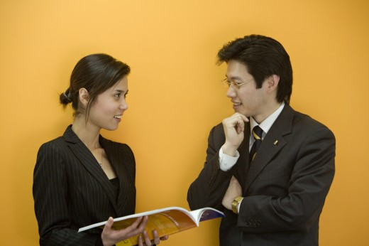 Stock Photo: 1574R-37247 Businesswoman holding a magazine and talking to a businessman